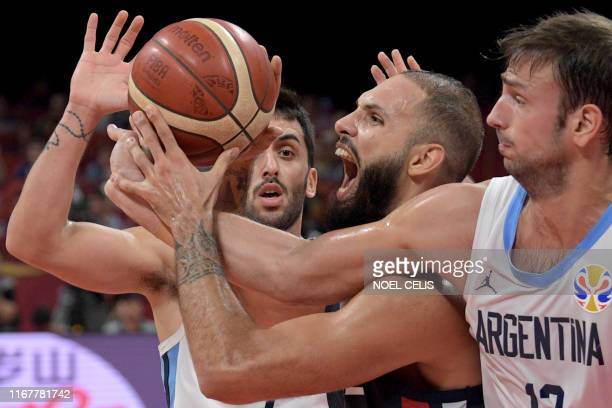 TOPSHOT France's Evan Fournier fights for the ball with Argentina's Marcos Delia during the Basketball World Cup semifinal game between Argentina and...