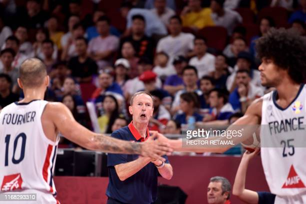 France's Evan Fournier shakes hands with his teammate Louis Labeyrie as their team coach Vincent Collet reacts during the Basketball World Cup third...