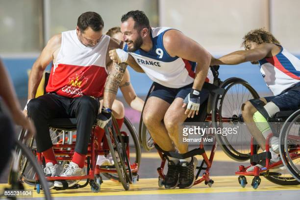 France's Fabian Frily gets a helping hand back into his chair after crashing by Canada's Tom Martineau during an Invictus Games Wheelchair Basketball...