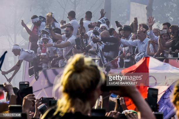 A France's fan takes pictures with her mobile phone of France's defender Adil Rami holding the trophy and celebrating with teammates on the roof of a...