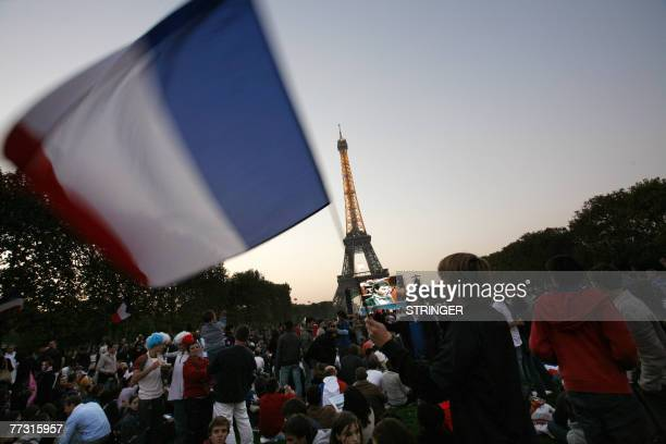 A France's fan waves a French flag on the ChampsdeMars near the Eiffel Tower center Paris during the rugby union World Cup 2007 semi final match...