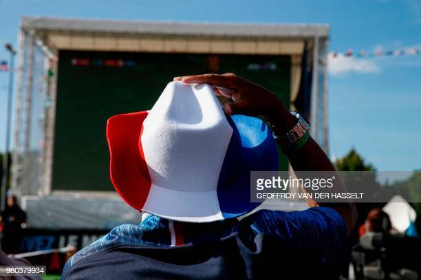 France's fan wearing a hat with the colours of the French national flag, watches on a giant screen the Russia 2018 World Cup Group C football match...