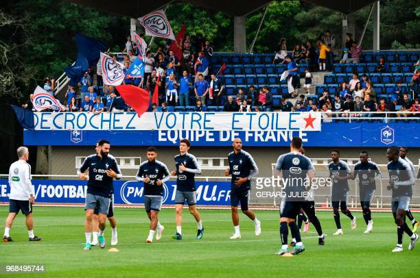 France's fans support cheer and hold a placard reading 'get your star' as they watch France's national football players taking part in a training...