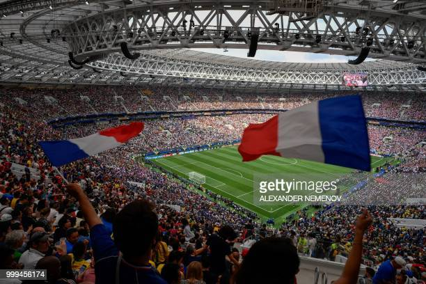 TOPSHOT France's fans wave French national flag as teams enters the football pitch prior to the Russia 2018 World Cup final football match between...