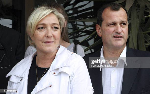 France's farright Front National party President Marine Le Pen flanked by Louis Aliot vicePresident of the party is pictured as she visits on June 11...