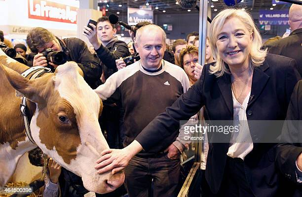 France's farright National Front party president Marine Le Pen pets a cow as she visits the Paris international agricultural fair at the Porte de...