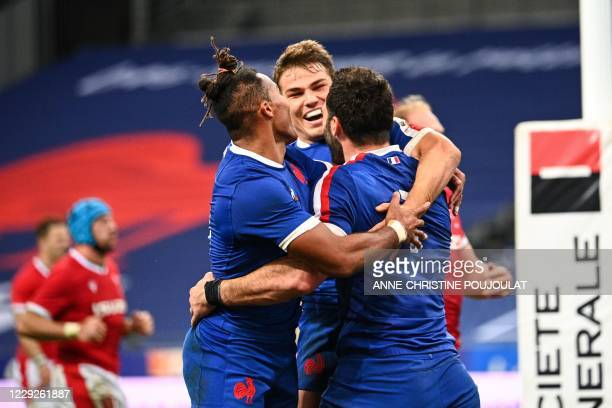 France's flanker Charles Ollivon celebrates with France's wing Teddy Thomas and France's scrum-half Antoine Dupont after scoring a try during the...