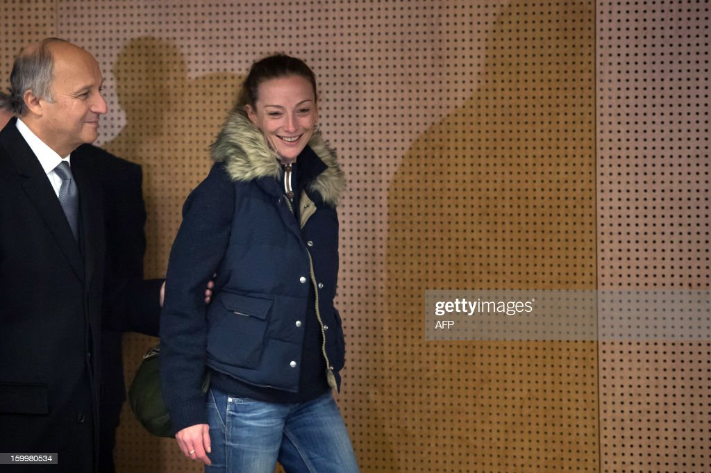 France's Florence Cassez, flanked by French Minister of Foreign Affairs Laurent Fabius (L), arrives at a press conference at Roissy airport on January 24, 2013 in Roissy-en-France where she landed after being freed from a Mexican prison the day before following a Supreme Court ruling that police violated her rights by staging her arrest for kidnapping on national television seven years ago. After facing 60 years in jail, Cassez, 38, took a flight to Paris, hours after three of five justices voted for her immediate release in a case that had strained Franco-Mexican ties.