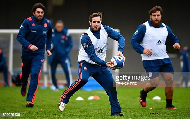 France's fly half Camille Lopez passes the ball next to assistant coach JeanFrederic Dubois and prop Xavier Chiocci during a training session on...