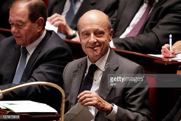 France's Foreign Affairs minister Alain Juppe gets the stem of his glasses in his mouth while sitting on the bench of the government during the...