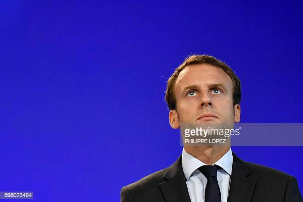 France's former Minister of the Economy Emmanuel Macron looks on after handling over power to French Minister of Finance and also current Minister of...