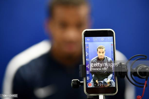France's forward Alassane Plea is seen on the screen of a smartphone as he poses in Clairefontaine-en-Yvelines on November 13 during the team's...