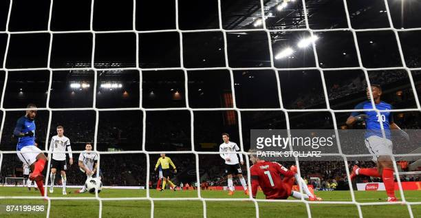 France's forward Alexandre Lacazette kicks the ball to score despite Germany's goalkeeper Kevin Trapp as France's forward Anthony Martial looks on...