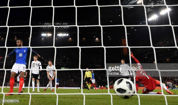 France's forward Alexandre Lacazette scores as Germany's goalkeeper Kevin Trapp looks on during the international friendly football match Germany...