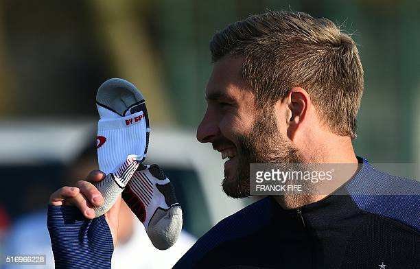 France's forward Andre Pierre Gignac smiles as he holds a sock before a training session in Clairefontaine en Yvelines on March 22 2016 ahead of the...