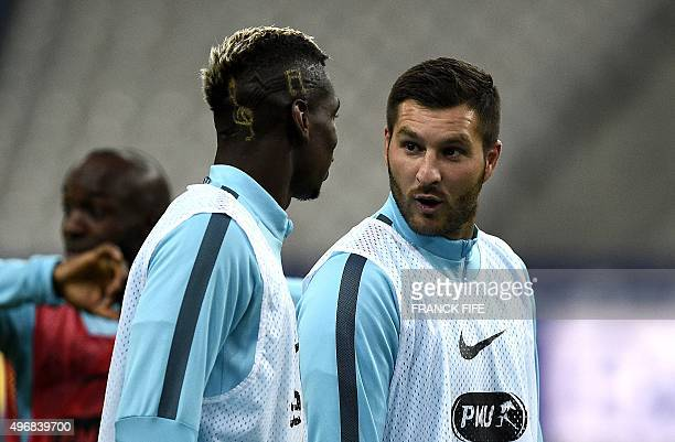 France's forward Andre Pierre Gignac speaks with France's midfielder Paul Pogba during a training session on November 12 2015 at the Stade de France...