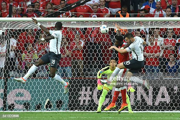France's forward AndrePierre Gignac and Switzerland's defender Johan Djourou jump for the ball during the Euro 2016 group A football match between...