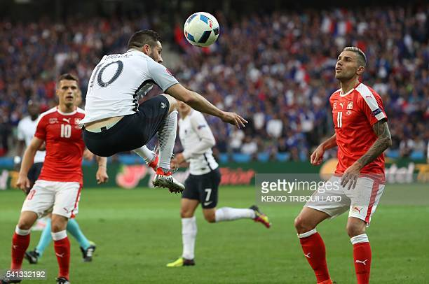 France's forward AndrePierre Gignac jumps for the ball next to Switzerland's midfielder Valon Behrami during the Euro 2016 group A football match...