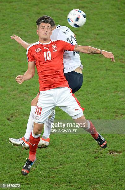 France's forward AndrePierre Gignac jumps for the ball with Switzerland's midfielder Granit Xhaka during the Euro 2016 group A football match between...