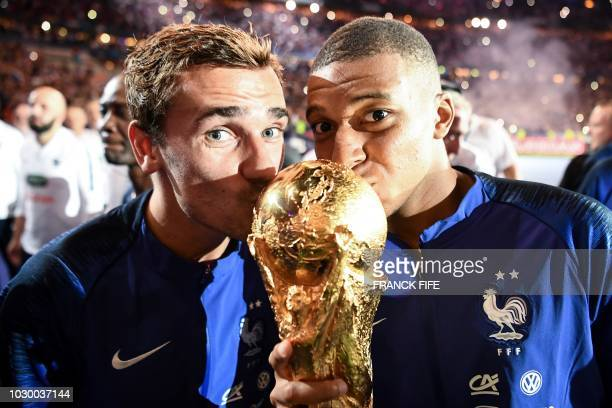 TOPSHOT France's forward Antoine Griezmann and France's midfielder Kylian Mbappe kiss the 2018 World Cup trophy as they celebrate during a ceremony...