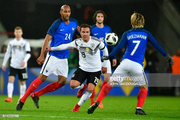 TOPSHOT France's forward Antoine Griezmann and France's midfielder Steven N'Zonzi vie for the ball with Germany's midfielder Mario Goetze during the...