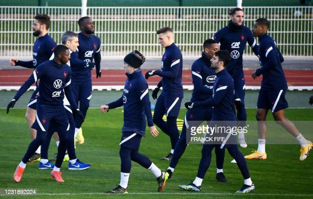 France's forward Antoine Griezmann and teammates warm up during a training session in Clairefontaine-en-Yvelines, near Paris on March 23, 2021 on the...