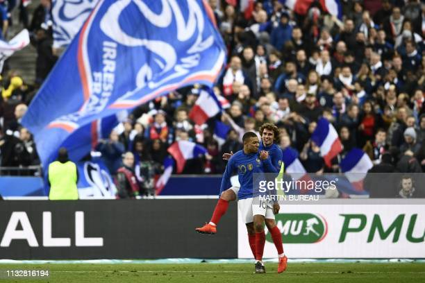 France's forward Antoine Griezmann celebrates after scoring the 40 goal with France's forward Kylian Mbappe during the UEFA Euro 2020 Group H...