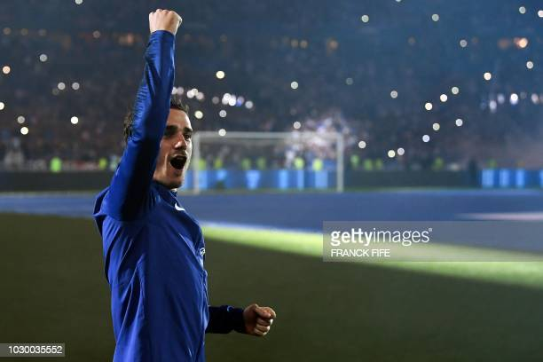 France's forward Antoine Griezmann celebrates as he arrives on the football picth during a ceremony to celebrate the victory of the 2018 World Cup...