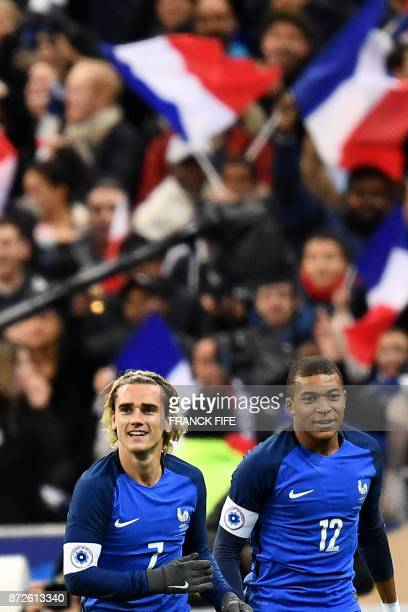 France's forward Antoine Griezmann celebrates next to France's forward Kylian Mbappe after scoring a goal during the friendly football match between...