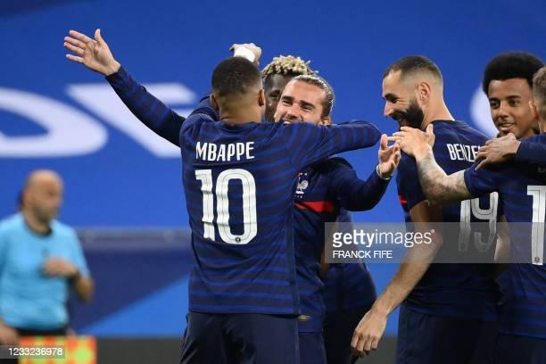 France's forward Antoine Griezmann celebrates with France's forward Kylian Mbappe and France's forward Karim Benzema after scoring his team's second...