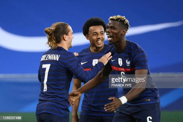 France's forward Antoine Griezmann celebrates with France's midfielder Paul Pogba after scoring his team's second goal during the friendly football...