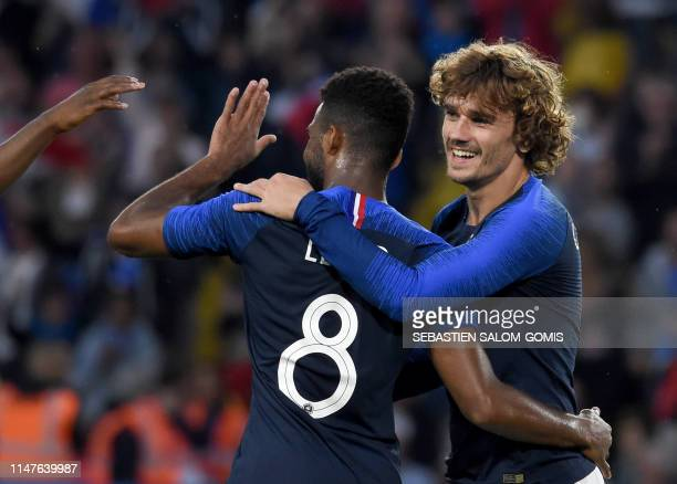 TOPSHOT France's forward Antoine Griezmann celebrates with his teammate France's forward Thomas Lemar after scoring a goal during the friendly match...