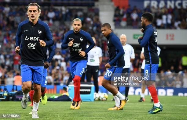 France's forward Antoine Griezmann defender Layvin Kurzawa and forward Kylian Mbappe warm up ahead of the the FIFA World Cup 2018 qualifying football...