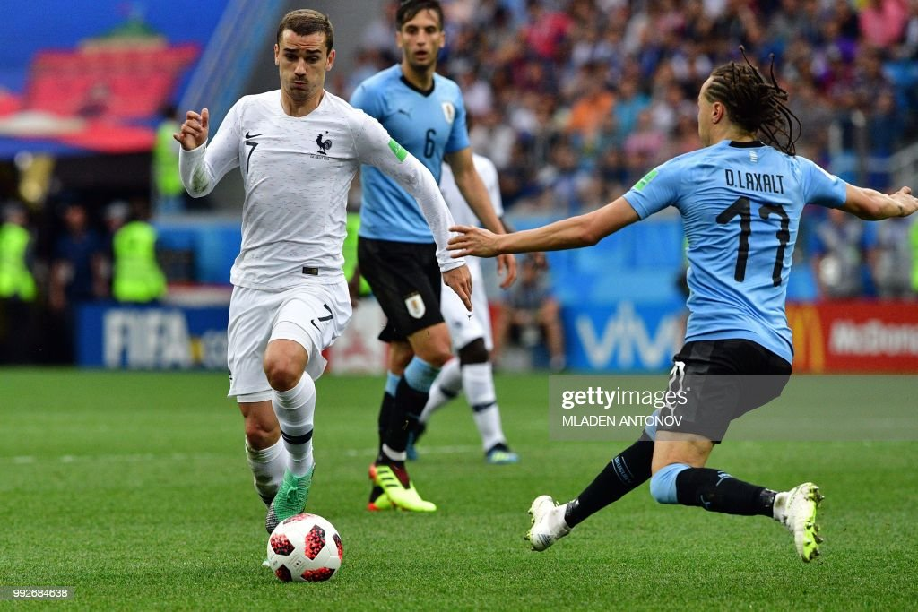 France's forward Antoine Griezmann (L) drives the ball past Uruguay's defender Diego Laxalt during the Russia 2018 World Cup quarter-final football match between Uruguay and France at the Nizhny Novgorod Stadium in Nizhny Novgorod on July 6, 2018.
