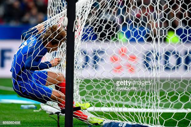 TOPSHOT France's forward Antoine Griezmann falls into the net of the goal during the friendly football match France vs Spain on March 28 2017 at the...
