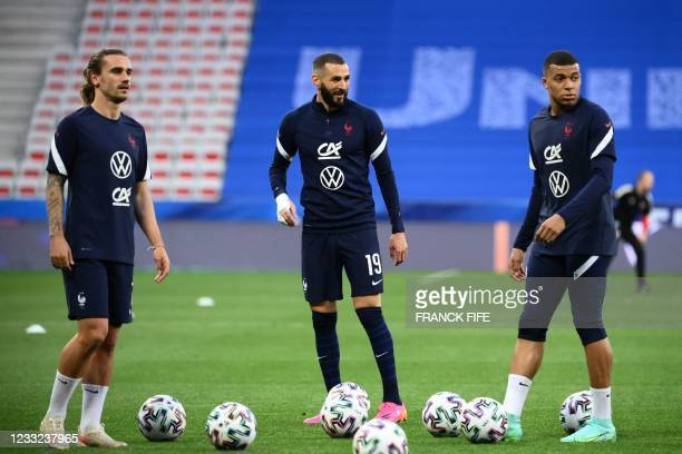 France's forward Antoine Griezmann, France's forward Karim Benzema and France's forward Kylian Mbappe warm up before the friendly football match...