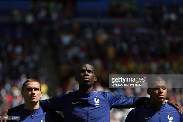 France's forward Antoine Griezmann, France's midfielder Paul Pogba and France's forward Kylian Mbappe listen to a national anthem before the Russia...