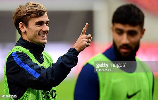 France's forward Antoine Griezmann gestures next to France's forward Nabil Fekir during a training session at the Amsterdam Arena in Amsterdam on...