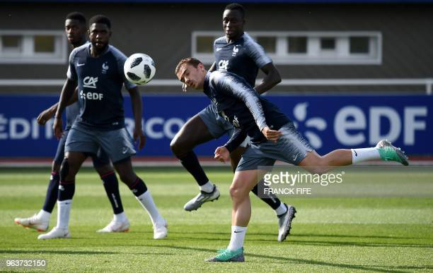 France's forward Antoine Griezmann heads the ball during a training session in Clairefontaine en Yvelines on May 30 as part of the team's preparation...
