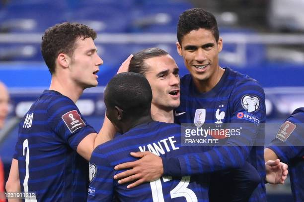France's forward Antoine Griezmann is congratulated by teammates after scoring a goal during the FIFA World Cup Qatar 2022 qualification football...