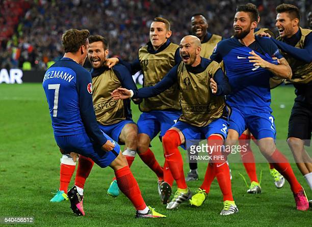 France's forward Antoine Griezmann is congratulated by teammates after scoring a goal during the Euro 2016 group A football match between France and...