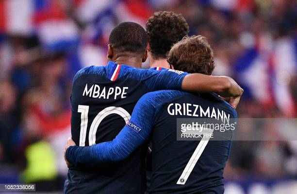 TOPSHOT France's forward Antoine Griezmann is congratuled by France's forward Kylian Mbappe after scoring a goal during the UEFA Nations League...