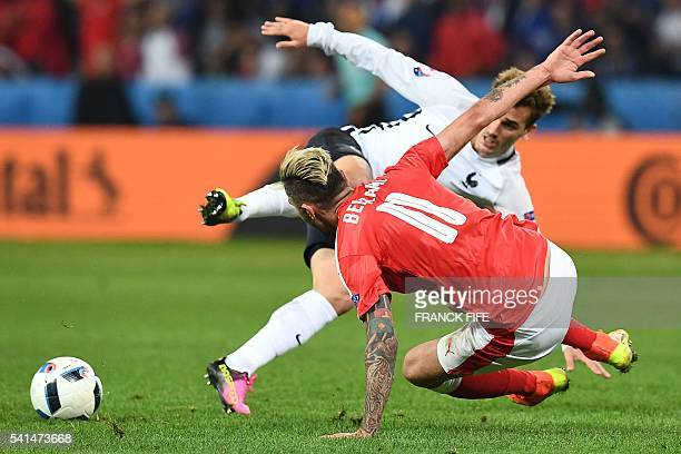 France's forward Antoine Griezmann is fouled by Switzerland's midfielder Valon Behrami during the Euro 2016 group A football match between...