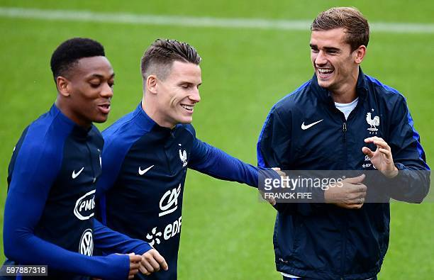 France's forward Antoine Griezmann jokes with forward Kevin Gameiro and forward Anthony Martial during a training session in...