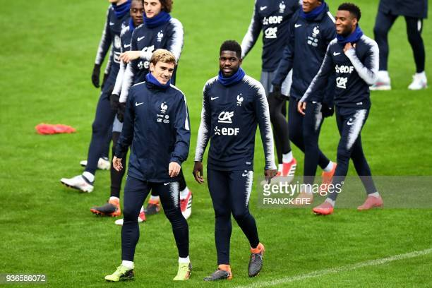 France's forward Antoine Griezmann jokes with France's defender Samuel Umtiti during a training session at the Stade de France in SaintDenis northern...