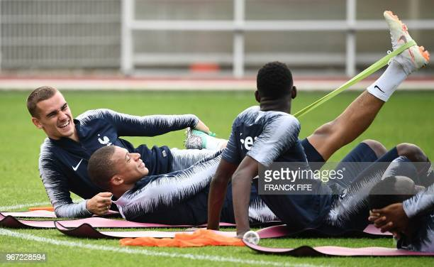 France's forward Antoine Griezmann jokes with France's forward Kylian Mbappe at the end of a training session in ClairefontaineenYvelines on June 4...