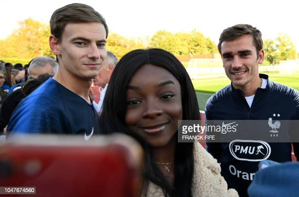France's forward Antoine Griezmann poses with a fan before a training session in Clairefontaine en Yvelines on October 8 ahead the unpcoming friendly...