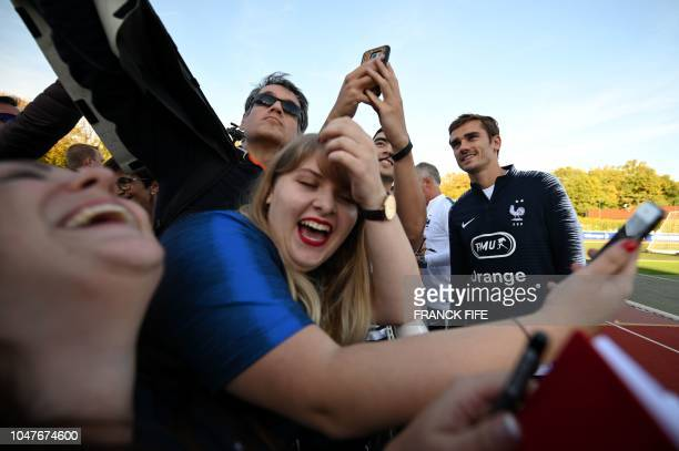 France's forward Antoine Griezmann poses with fans before a training session in Clairefontaine en Yvelines on October 8 ahead the unpcoming friendly...