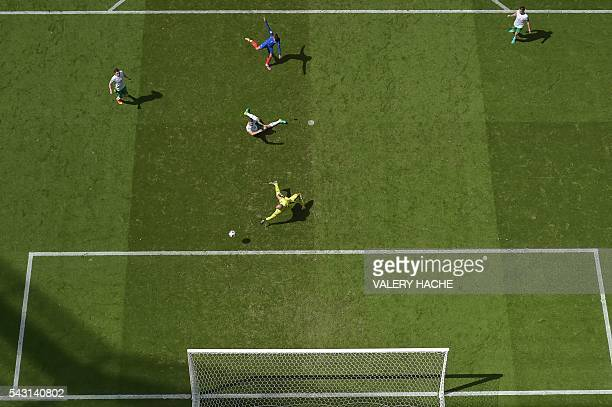 France's forward Antoine Griezmann scores against Ireland's goalkeeper Darren Randolph during the Euro 2016 round of 16 football match between France...