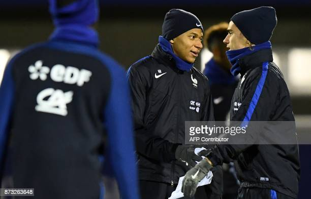 France's forward Antoine Griezmann speaks with France's forward Kylian Mbappe during a training session in ClairefontaineenYvelines on November 12 as...